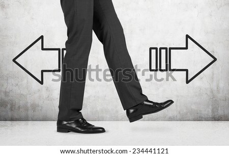 Businessman and arrows 'left or right'. a person is making a step.  - stock photo
