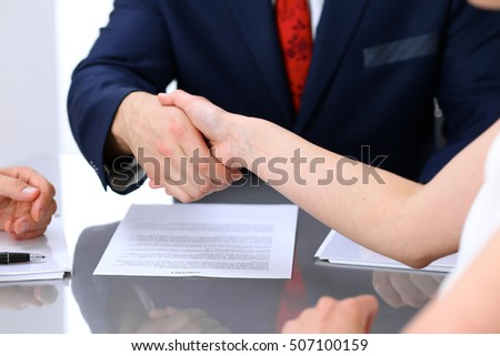 Businessman and business woman shaking hands to each other above signed contract