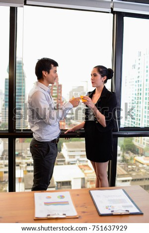 businessman and businesswoman are drinking champagne talking and smiling while celebrating in office, successful business concept.