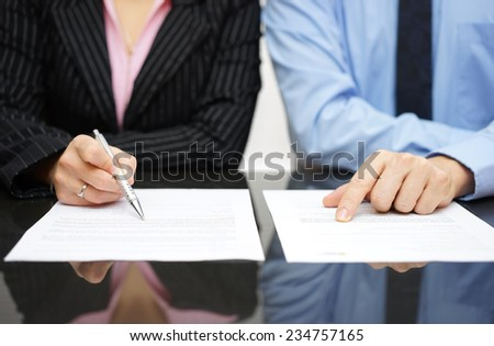 businessman and businesswoman are inspecting  contract - stock photo