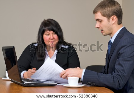 Businessman and businesswoman at meeting with laptop in office