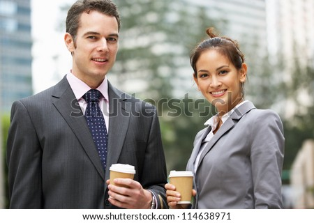 Businessman And Businesswoman Chatting In Street Holding Takeaway Coffee