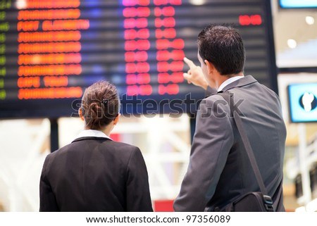 businessman and businesswoman checking flight information at airport - stock photo