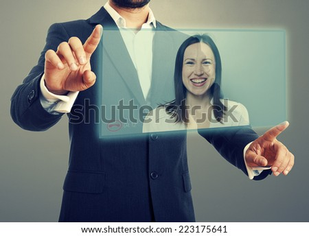 businessman and businesswoman communicating through video chat on virtual device. photo over dark background - stock photo