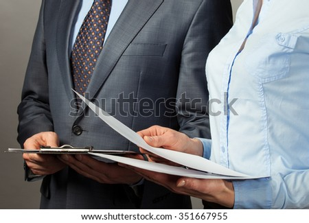 Businessman and businesswoman discuss a plan of work, grey background - stock photo