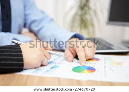 businessman and businesswoman discussing about company report in office - stock photo