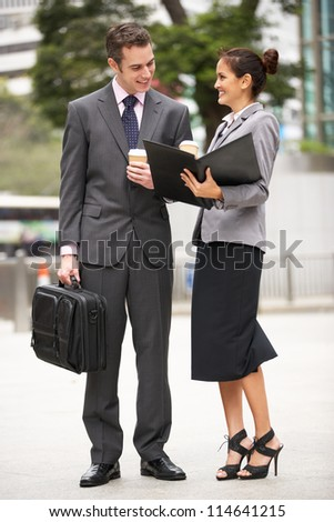 Businessman And Businesswoman Discussing Document In Street Holding Takeaway Coffee - stock photo