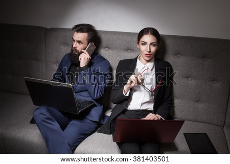 businessman and businesswoman dressed in suit and with laptop, phone and tablet; corporate workers with portable computers and devices;