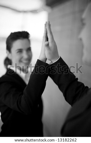 businessman and businesswoman dressed in suits giving high-five