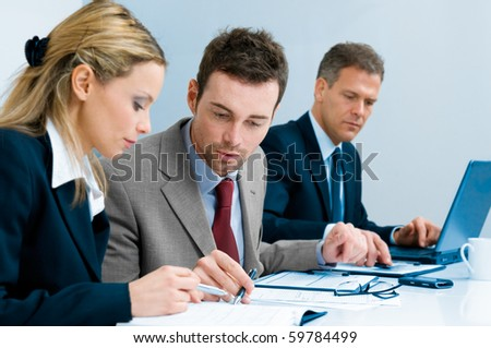 Businessman and businesswoman examining together a document during a working meeting in office