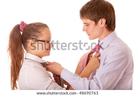 Businessman and businesswoman fasten each other ties, isolated on white background.