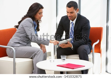Businessman And Businesswoman Having Informal Office Meeting