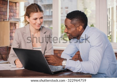Businessman and businesswoman having meeting in office. Young business people discussing something while looking at the computer monitor together - stock photo