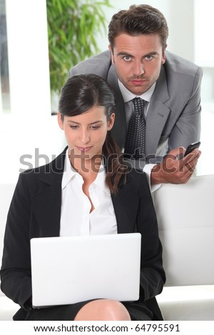 Businessman and businesswoman in front of a laptop computer
