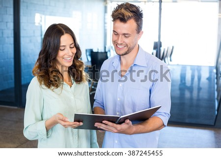 Businessman and businesswoman interacting holding organizer in office