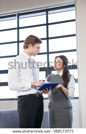 Businessman and businesswoman interacting using digital tablet in the office - stock photo