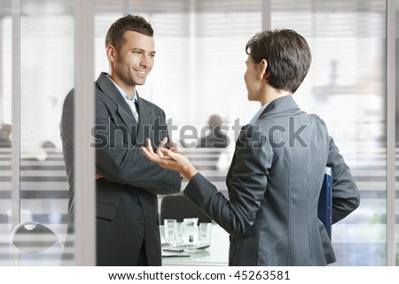 Businessman and businesswoman leaving meeting room, talking at the door, smiling. - stock photo