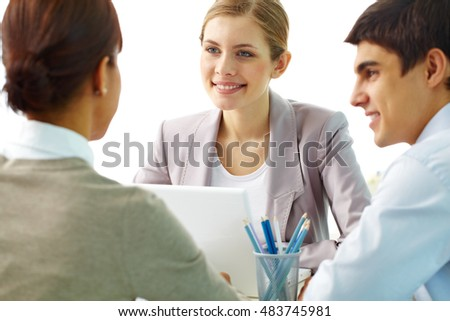 Businessman and businesswoman listening to their colleague and smiling