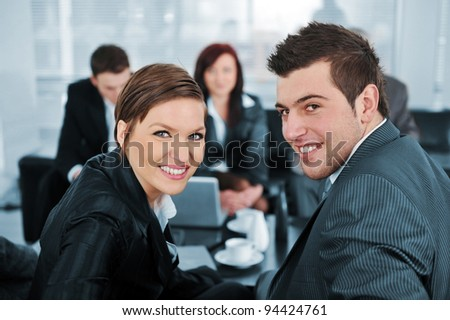 Businessman and businesswoman looking at camera at office meeting