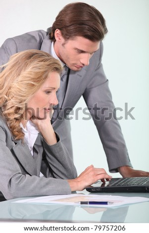 businessman and businesswoman looking at laptop - stock photo