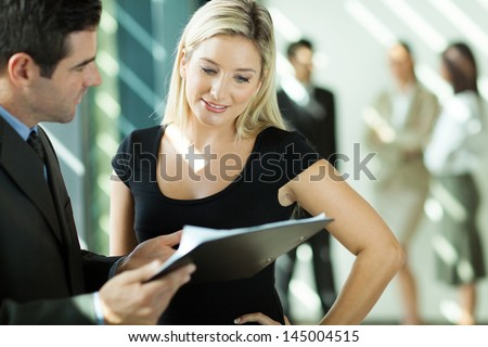 businessman and businesswoman looking at the document in office - stock photo