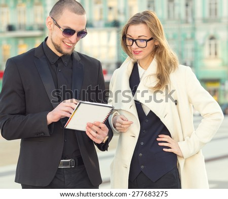 Businessman and businesswoman meeting. Business meeting manager and the client on the background of business office buildings downtown. They discuss the contract or insurance policy. Business people.