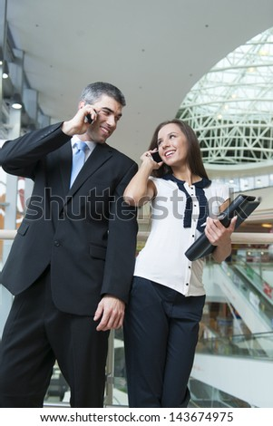 Businessman and businesswoman on mobile phones - stock photo