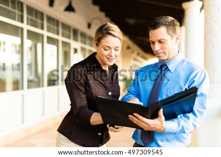 Businessman and businesswoman outside offices