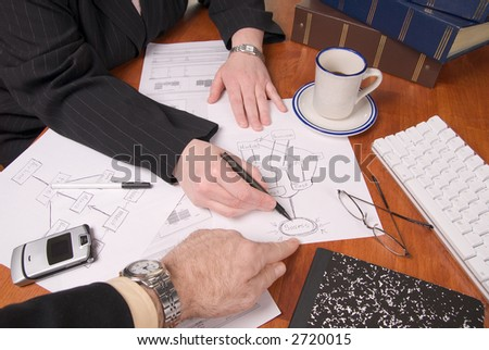 Businessman and businesswoman planning growth strategies on a table with business tools - stock photo