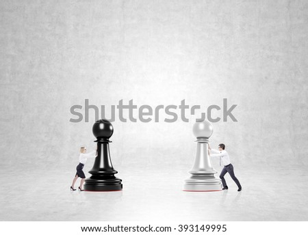 Businessman and businesswoman pushing black and white pawns to each other. Concrete background. Concept of business game. - stock photo