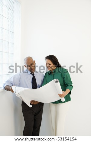 Businessman and businesswoman reading architectural blueprint plans and smiling. - stock photo