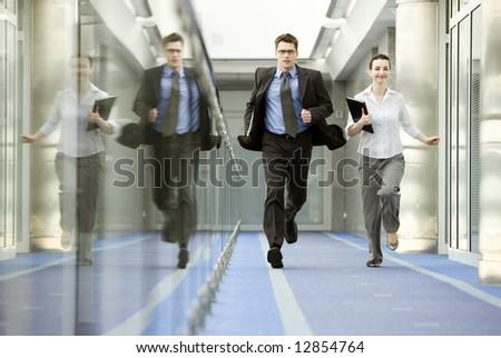Businessman and businesswoman running on modern office corridor. - stock photo
