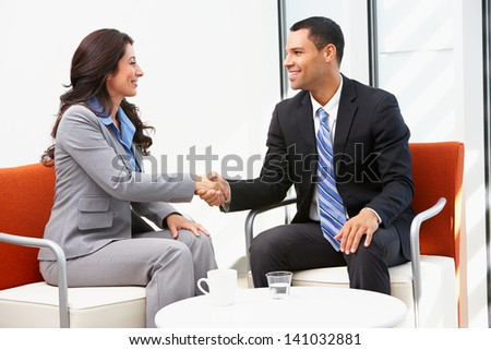 Businessman And Businesswoman Shaking Hands After Meeting - stock photo