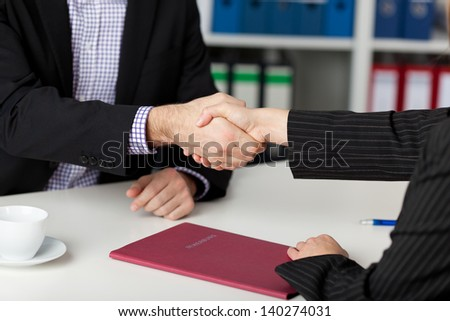 Businessman and businesswoman shaking hands at office desk - stock photo