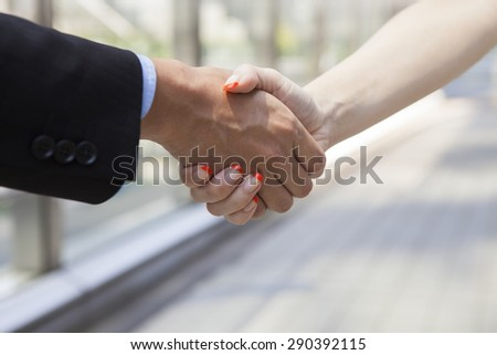 Businessman And Businesswoman Shaking Hands In Street - stock photo