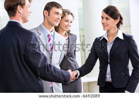 Businessman and businesswoman shaking hands in the hall