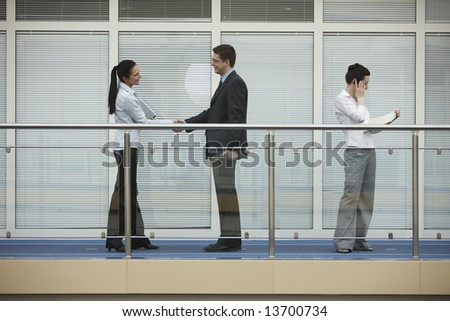 Businessman and businesswoman shaking hands on modern office corridor. tree persons - stock photo