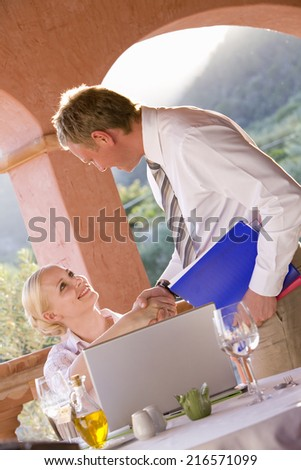 Businessman and businesswoman shaking hands on restaurant balcony