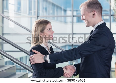 Businessman and businesswoman shaking their hands