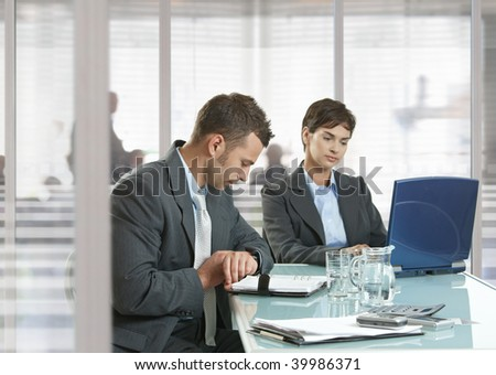 Businessman and businesswoman sitting at desk in office, using laptop computer and checking time. - stock photo