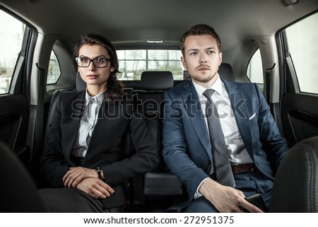 businessman and businesswoman sitting in a limousine. Young businesswoman and businessman in back seat of car - stock photo