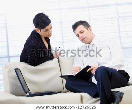 Businessman and businesswoman sitting of sofa at office in front of window and working together, doing paperwork, serious.