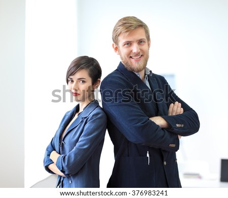 Businessman and businesswoman standing back to back with crossed arms in the office. Team work concept - stock photo