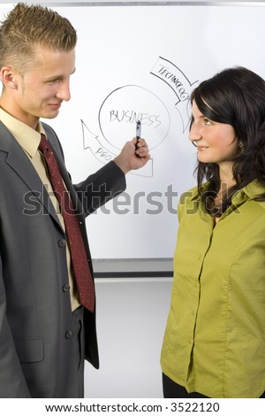 Businessman and businesswoman standing in front of the blackboard. Looking at each others. Side view. Gray background - stock photo