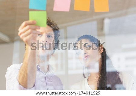 Businessman and businesswoman sticking adhesive notes on glass wall in office - stock photo