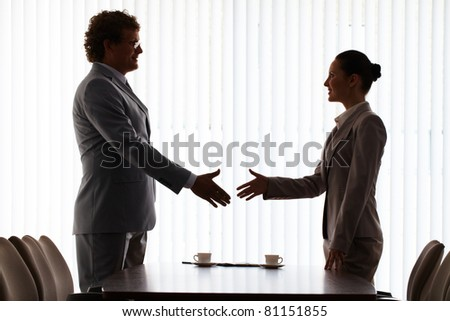 Businessman and businesswoman stretching hands for handshake - stock photo