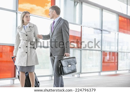 Businessman and businesswoman talking while walking on railroad platform - stock photo