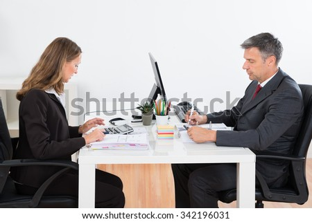 Businessman And Businesswoman Together Calculating Finance At Desk - stock photo