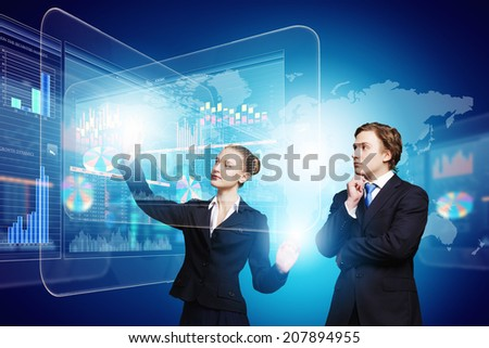 Businessman and businesswoman touching icon of digital screen - stock photo