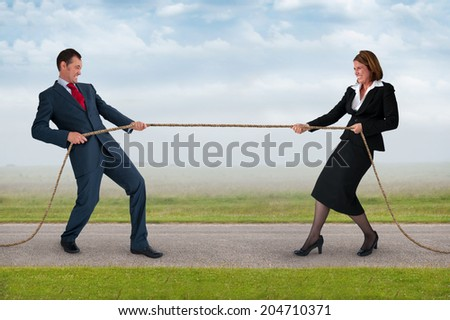 businessman and businesswoman tug of war contest of strength - stock photo